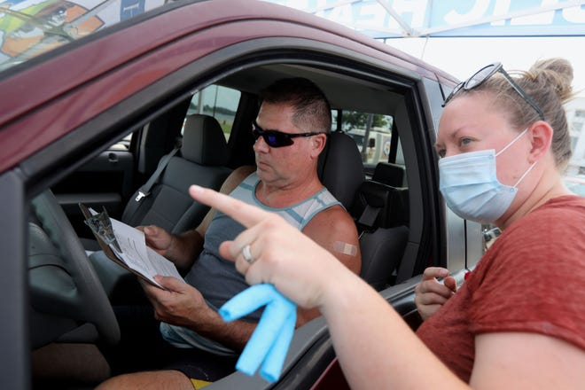 Mark Walz of Burlington looks over some paperwork Friday after getting a shot from Sam Sweeney, a registered nurse with the Des Moines County Public Health Department, during a drive-thru COVID-19 vaccination clinic in the parking lot of Memorial Auditorium.