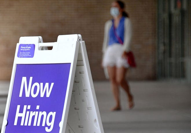 """A """"Now Hiring"""" sign appeals for job-hunters outside a store in Arlington, Va."""