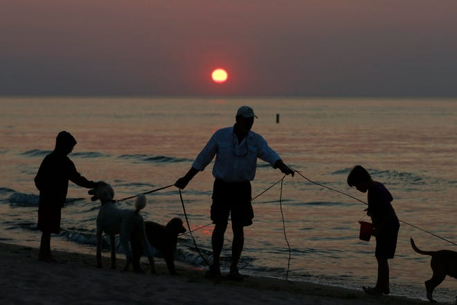 People and dogs along the beach are silhouetted against Lake Michigan as the sun appears through the haze emitted from the American West, Tuesday, July 27, 2021, in Indiana Dunes State Park, in Indiana. Wildfires in the western U.S. created hazy skies as far away as New York.