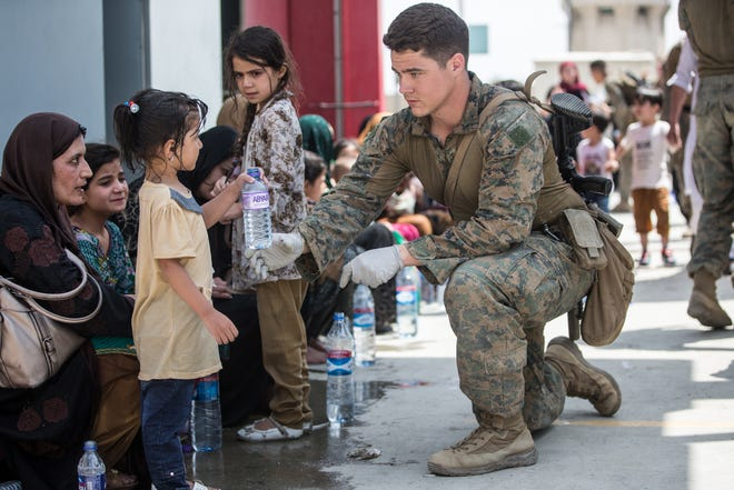A Marine with the 24th Marine Expeditionary Unit, based out of Marine Corps Base Camp Lejeune, provides fresh water to a child during evacuations at Hamid Karzai International Airport, Kabul, Afghanistan, Aug. 20, 2021.