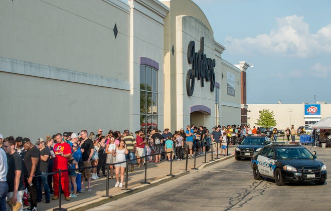 """Hundreds of fans of Curtis """"50 Cent"""" Jackson line up on the sidewalk outside Hy-Vee and the former Gordmans store Friday in North Peoria. The popular rapper was in town to promote his line of liquors, Branson Cognac and Le Chemin du Roi Champagne, and to sign autographs."""