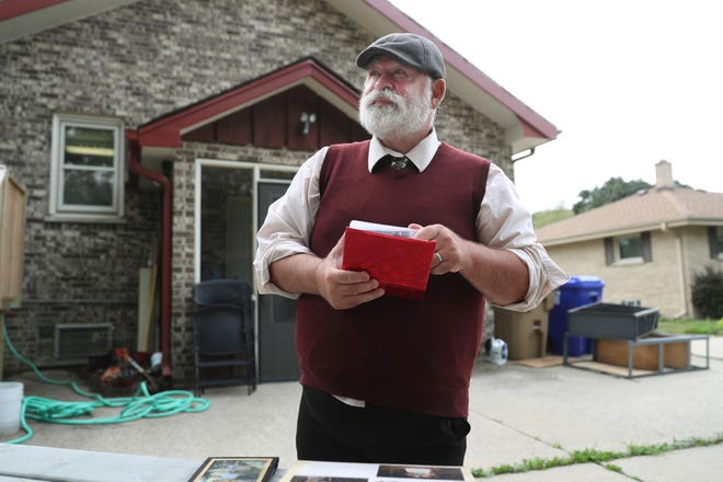Gary Eckstein looks through family photo albums at home on Aug. 12, 2021, in Kenosha, Wisconsin. Eckstein's mother, Arlene Boetcher, 85 and unvaccinated, died from complications of COVID-19, he said.