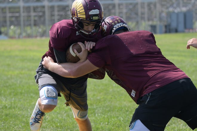 Schuyler County sophomore Aden Snider carries the ball during a drill at practice on Aug. 18, getting tackled by junior Hayden Dixon.