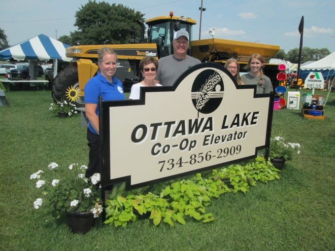 Jason Heerdegen (center), manager of the Ottawa Lake Co-Op Elevator, stands behind a sign marking the co-op's exhibit at the Monroe County Fair that took first place among farm dealerships. With him are (from left) his wife, Alisa; mother, Suzanne (Bischoff) Keller; and two daughters, Lauren, 15, and Alison, 17.