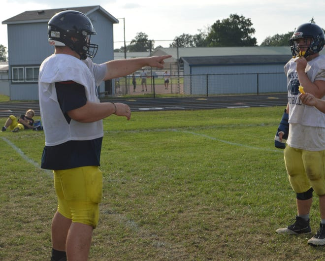 Noah Bauman, Whiteford's two-time All-Stater, points out blocking assignments for the offensive line during a drill at practice. Across from him is Brayden Luse.