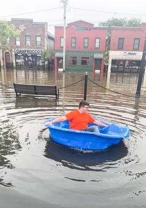 Kaiden Vaughn, 17, floats down a flooded street in a kiddie pool in Rome.