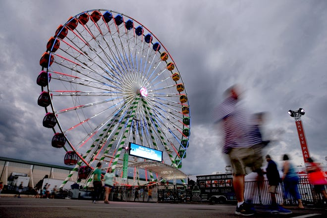 People walk by the Sky Eye Ferris Wheel at the 2019 Oklahoma State Fair.