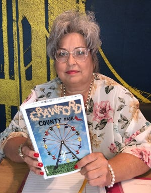 Crawford County Fair board member Marla Keady holds a copy of this year's program for the fair. The cover was designed by Alma High School sophomore Baleigh McCabe.