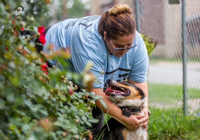 Ramona Cruz interacts with Pinto, her family's dog that was recently recovered from a steep riverbank after getting loose, on Friday outside their home in South Bend.