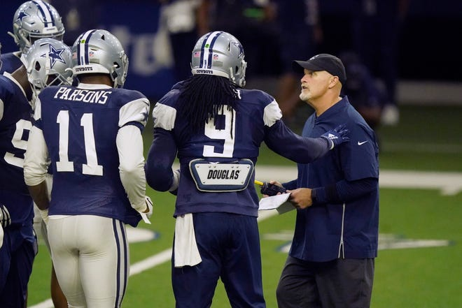 Dallas Cowboys defensive coordinator Dan Quinn, right, makes a point with linebackers Jaylon Smith (9), Micah Parsons and others during during NFL football practice in Frisco on Wednesday.