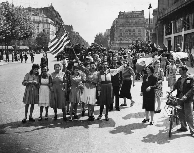 In this Aug. 25, 1944 photo, French civilians with hastily made American and French flags greet U.S. and Free French troops entering Paris after the Allied liberation of the French capital from Nazi occupation in World War II.