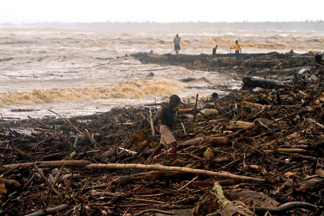 A child walks at a beach covered by debris after the passing of Hurricane Irene in Nagua, in the northern coast of the Dominican Republic, on Aug. 23, 2011.