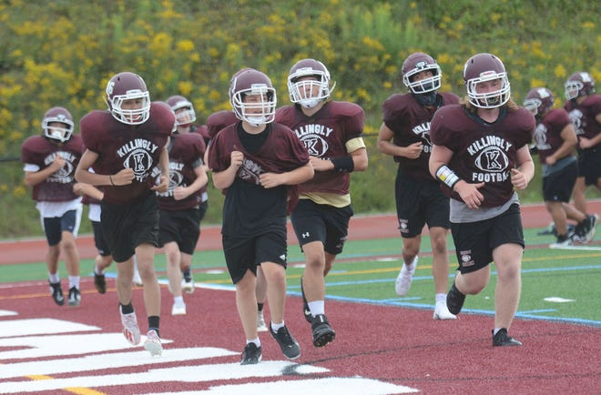 Killingly High School players prepare for the 2021 season by running a lap Thursday during practice in Dayville.