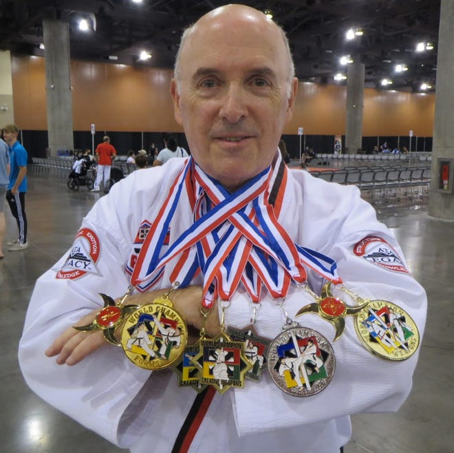 Dr. Robert McGee, an accounting professor at Fayetteville State, shows off his haul of eight medals from the Taekwondo World Championship, held in Phoenix, Arizona,  July 28-30. Events he medaled in were traditional, creative and extreme disciplines of weapons and forms, along with sparring and combat weapon sparring.