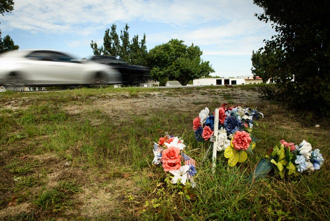 Traffic races past a roadside memorial for an unknown person on Gillespie Street, near where deadly hit-and-runs have taken place.