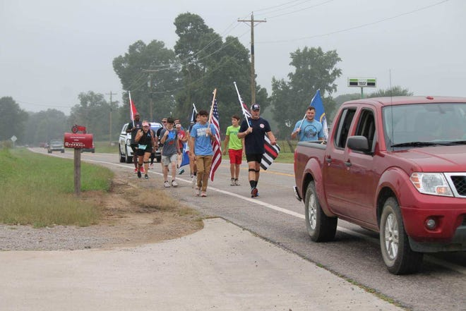 People walk part of the 22 miles between the Paris and Booneville courthouses on Sept. 11, 2020, to commemorate the day. This year, people will walk from the Paris Courthouse to the New Blaine Veterans of Foreign Wars.