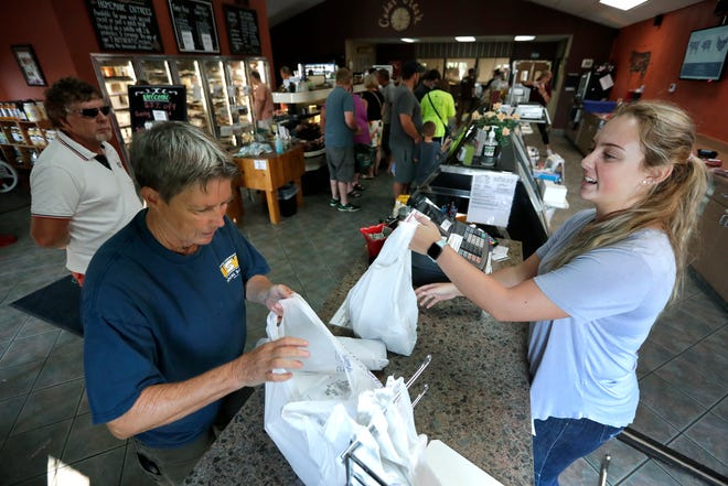 Cindy Buman, left, of Mackville purchases items from Mackenzie Ostrander, an employee at Cedar Creek Marketplace, on Friday.