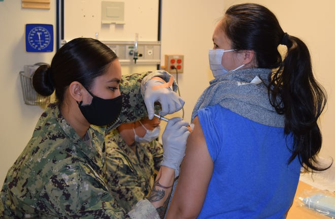 Hospital Corpsman 2nd Class Brittany Vain provides the COVID-19 vaccine to Anh Nguyen, staff pharmacist on Dec. 29, 2020, at NHB/NMRTC Bremerton. Then, as now, Vain augmented the command's preventive medicine technicians (PMT) during a mass vaccination evolution. As a ready medical force, the PMTs are again preparing to administer vaccine on a wide scale to those in need as Secretary of Defense Lloyd Austin addressed all Department of Defense employees – active duty, civilian and contractor personnel – in a memorandum he will ask the president, no later than the middle of September, to make the COVID-19 vaccine mandatory. The actual vaccine mandatory date could become sooner if the Food and Drug Administration gives a final approval for the vaccine(s) or if the highly transmissible Delta variant of the virus continues to elevate infection rates.
