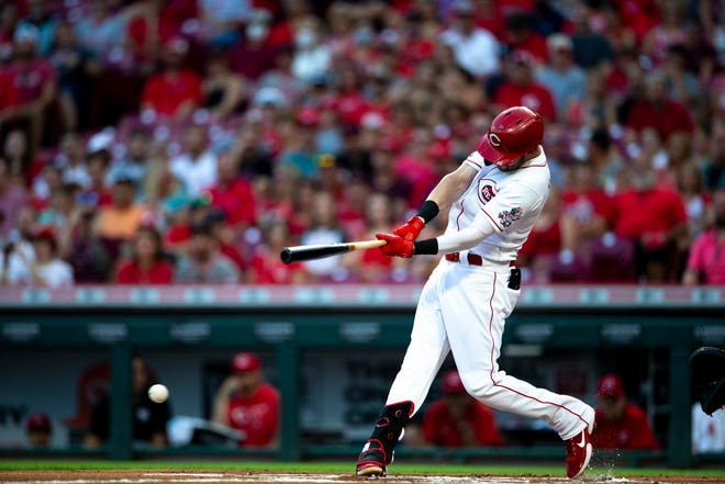 Cincinnati Reds center fielder Tyler Naquin (12) hits a triple in the first inning of the MLB baseball game between the Cincinnati Reds and the Miami Marlins on Friday, Aug. 20, 2021, at Great American Ball Park in Cincinnati.