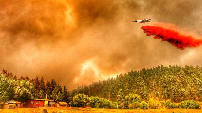 An air tanker drops flame retardant on the Richard Spring Fire southwest of Colstrip on Thursday, Aug. 16
