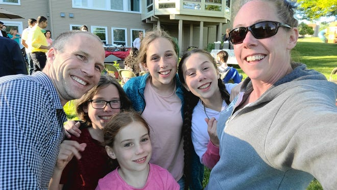 Matt and Amy McKenna pose for a photo with their four children, Asher, 9, Fiona, 7, Sophia, 13, and Penelope, 11, while celebrating Matt's graduation from residency on June 13, 2020.