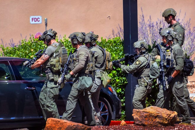 Tactical officers search for a suspect after a shootout that left multiple officers injured in northeast Albuquerque, N.M. on Thursday, Aug. 19, 2021.