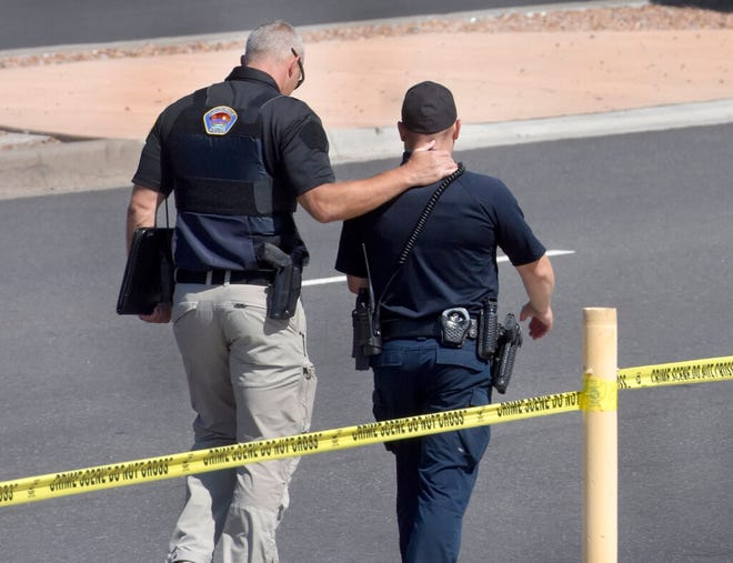Two officers walk away from the scene after a shootout that left multiple officers injured in northeast Albuquerque, N.M. on Thursday, Aug. 19, 2021.