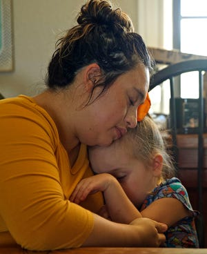 Jessica Wallace hugs her daughter Aubrey after a video call with her husband Caleb who is in the ICU at Shannon Medical Center with COVID-19 on Thursday, Aug. 19, 2021. Caleb Wallace was heavily sedated at the time and was not able to respond to them during the call.