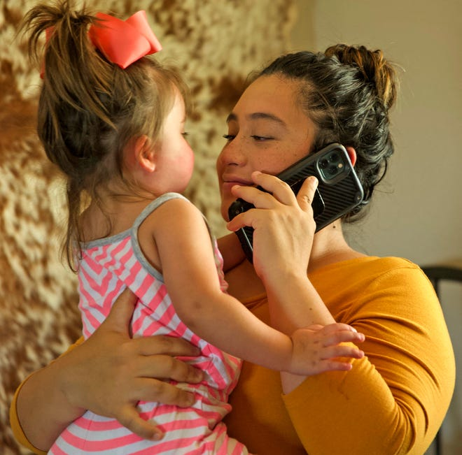 Jessica Wallace, right, smiles at her daughter Kate, left, as she tries to set up a video call with her husband Caleb Wallace who is in the ICU at Shannon Medical Center with COVID-19 on Thursday, Aug. 19, 2021.
