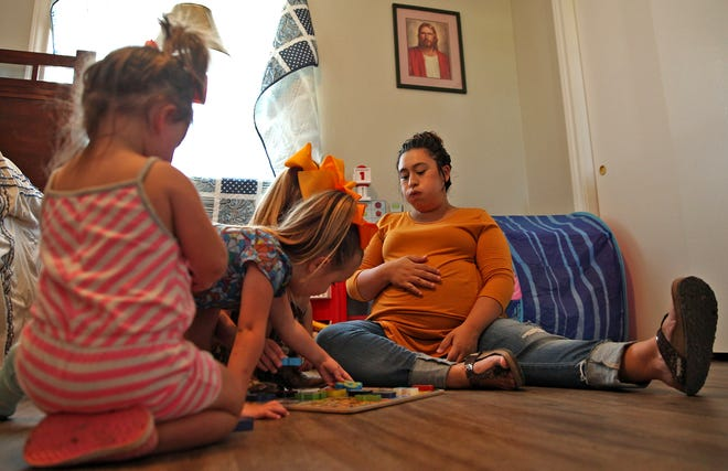Jessica Wallace, right, plays a game with her three daughters at her in-laws' home north of San Angelo on Thursday, Aug. 19, 2021.