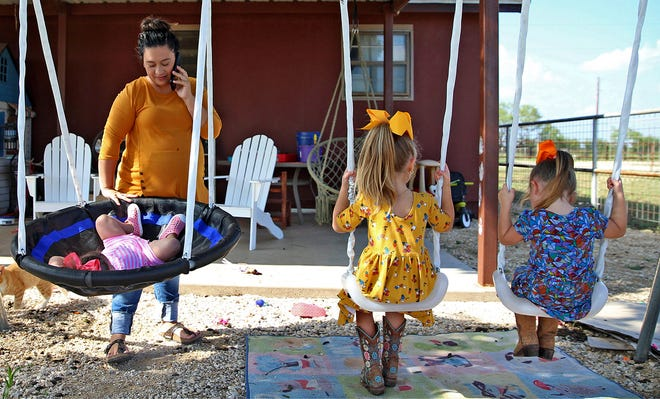 Jessica Wallace, far left, talks on the phone to her in-laws while, from left: Kate, Brooke and Aubrey Wallace play in the back yard of their home north of San Angelo on Thursday, Aug. 19, 2021.