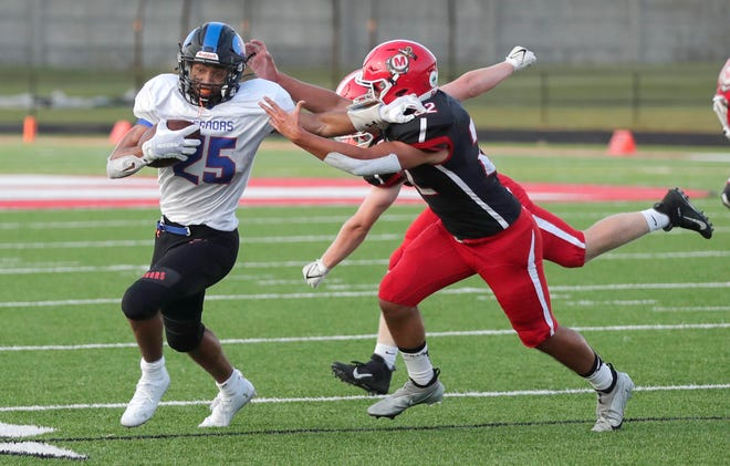 Appleton West's Ben Vallafskey, left, fights off a tackle attempt against Manitowoc Lincoln during last week's season opener in Manitowoc.