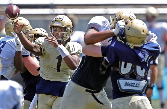 University of Akron quarterback Kato Nelson, left, gets a pass off during football practice Saturday at InfoCision Stadium. [Jeff Lange/Beacon Journal]