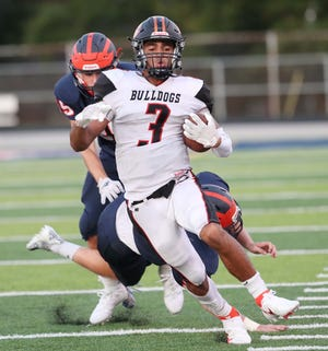 Green's Trey Martin evades Ellet's Cameron Hinkle, left, and Aiden Roberts on a punt return for a touchdown during the second quarter of their game at Ellet High School Friday, Aug. 20, 2021 in Akron, Ohio.