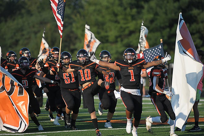 Marlington's Christio'n Hicks (1) leads the Marlington Dukes on to the field for a non-conference game against Coventry Friday, August 20, 2021 at Marlington High School.