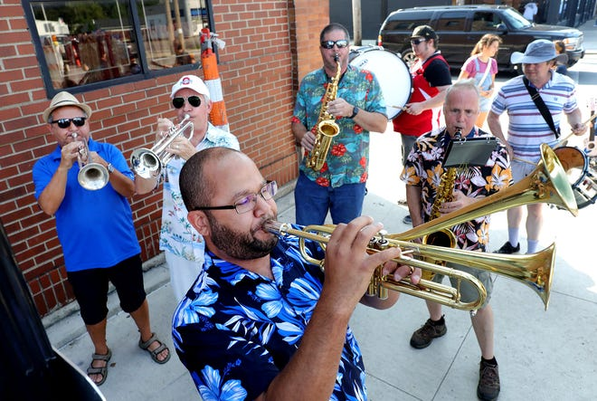 Musical director Martin Williams, center foreground, plays his double-bell trumpet along with the other members of the Nationwide Children's Hospital Orchestra (NACHO) Street Band during the Avenue for All Festival on Saturday on Parsons Avenue.
