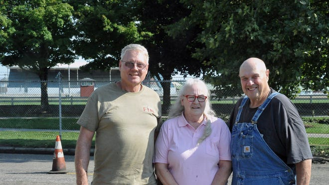 Mary Trotter with friends Jeff Harmon and Ron Grosjean and the Wayne County Fair grandstand in the background. After 25 years as a fair parking official, Trotter will retire after this year's fair, which is Sept. 11-16.