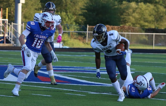 Chase running back Marqies McCombs breaks away from West Henderson's Caleb Collany (21) as West's Gavin Russell closes in during a game earlier this season at West.