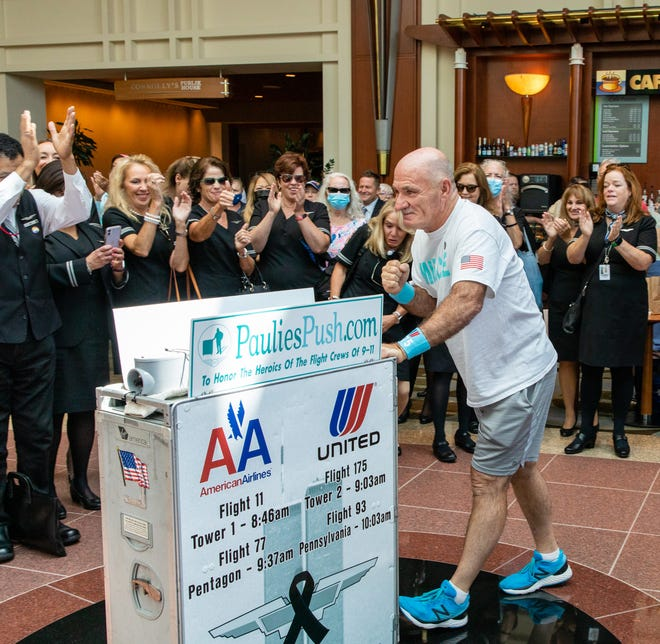 Paulie Veneto, a former United Airlines flight attendant, pushes an airline service cart through the Hilton lobby as he is cheered on by United Airlines flight attendants, friends and family on Saturday, Aug. 21, 2021.