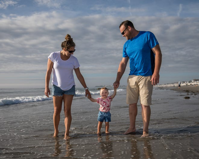Christina Parisi and Jamie Gosselin of Hampton take their daughter, Sydney, for a morning walk at low tide on Hampton's North Beach Saturday, Aug. 21, 2021.