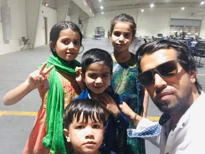 Amin Faqiry and his four children in the dining hall of the military camp in Qatar where they are being housed.