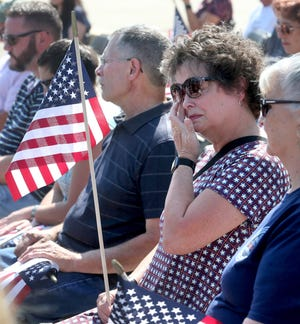 Kathy Patron holds the American flag and wipes away a tear during a 10th anniversary memorial service for her son Marines Sgt. Daniel Patron in Perry Township on Saturday, Aug. 21, 2021. Patron died Aug. 6, 2011, while defusing a roadside bomb while serving in Afghanistan.