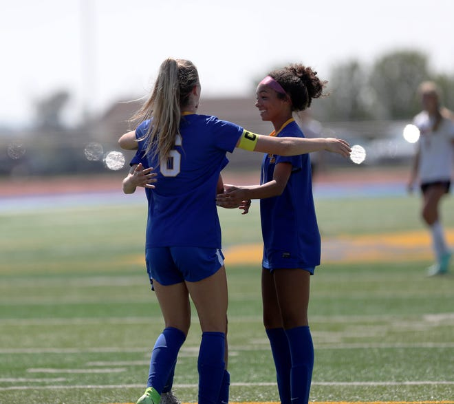 Aberdeen Central midfielder Morgan Fiedler (6) embraces teammate Deshani Peters after Fiedler scored the first goal of the game in the 26th minute of Saturday's game at Swisher Field. American News photo by Jenna Ortiz, taken 08/21/2021.