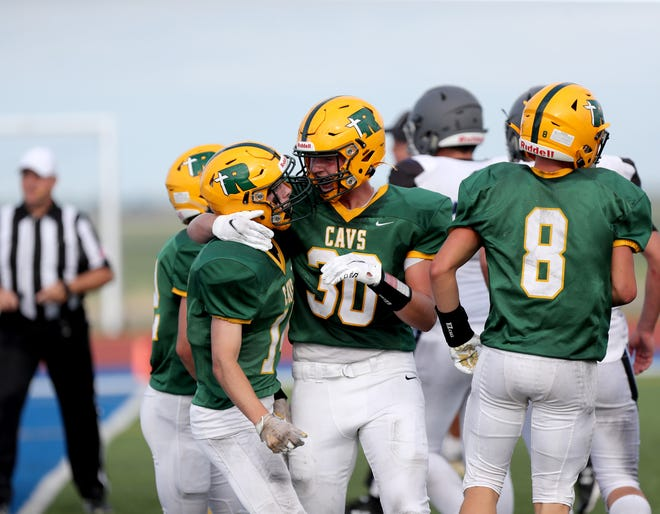 Aberdeen Roncalli fullback Kayden Clark, center, celebrates with wide receiver Andrew Brennan after Brennan returned an interception for a touchdown against St. Thomas More in the second quarter of Friday's game at Swisher Field. American News photo by Jenna Ortiz, taken 08/20/2021.