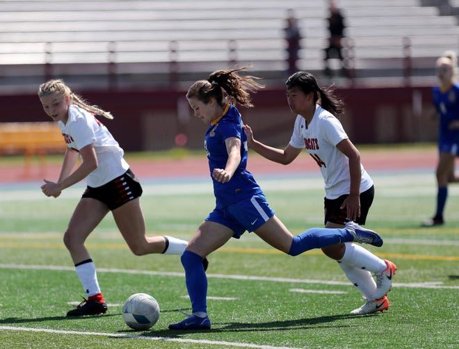 Aberdeen Central forward Lauren Joosten goes through Brookings defender Ella Kjelden, left, and forward Elly Stahl to put a shot in the net in the first half of Saturday's game against Brookings at Swisher Field. American News photo by Jenna Ortiz, taken 08/21/2021.