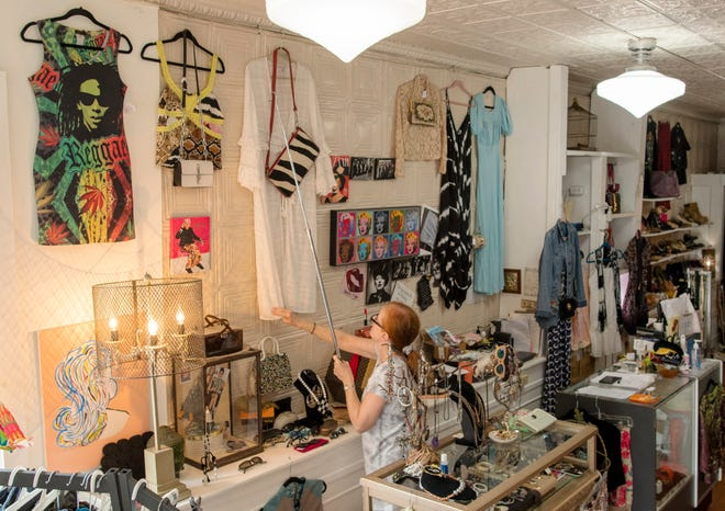 Maria Pappas changes the dresses on display inside her consignment shop Modern Muse Friday on Highland Street.
