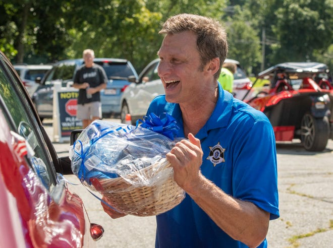 Worcester County Sheriff Lew Evangelidis gives a driver a raffle basket won at the drive-through senior picnic Saturday at SAC Park.
