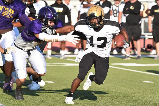 Abilene HIgh's Da'King Thomas (12) tries to break away from a Wylie defender during Friday's scrimmage at Sandifer Stadium. Thomas scored a pair of touchdowns during controlled play and one during the live quarter. The Eagles travel to Amarillo Tascosa for the season opener Friday.