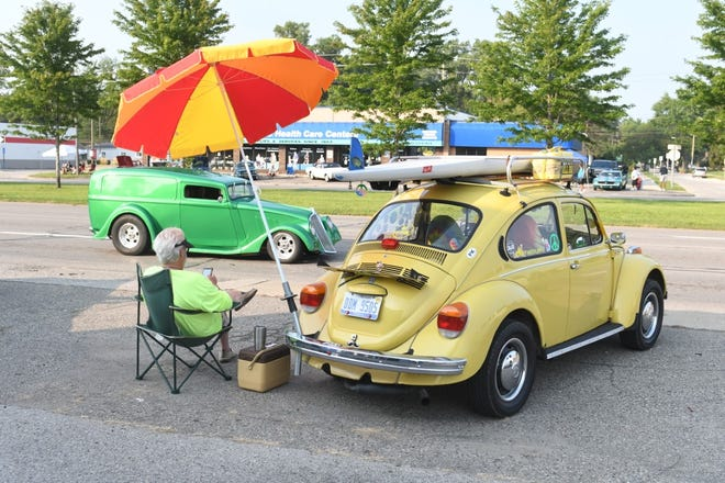 Garry Hogness of Goodrich watches classic cars pass along Woodward Avenue as he sits with his 1972 VW Beetle in Royal Oak for the Woodward Dream Cruise Saturday.