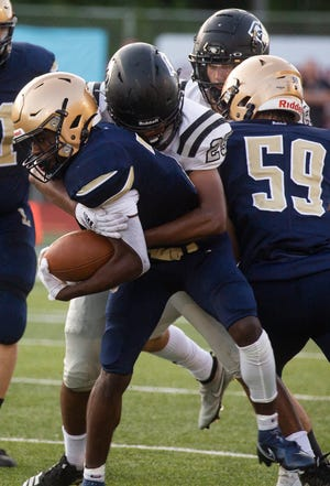 Lancaster senior running back Nasir Robinson fights for yardage during the Golden Gales' first game of the season against Pickerington North. Robinson helped lead Lancaster to their first victory of the season last week in a 34-15 win over Olentangy.
